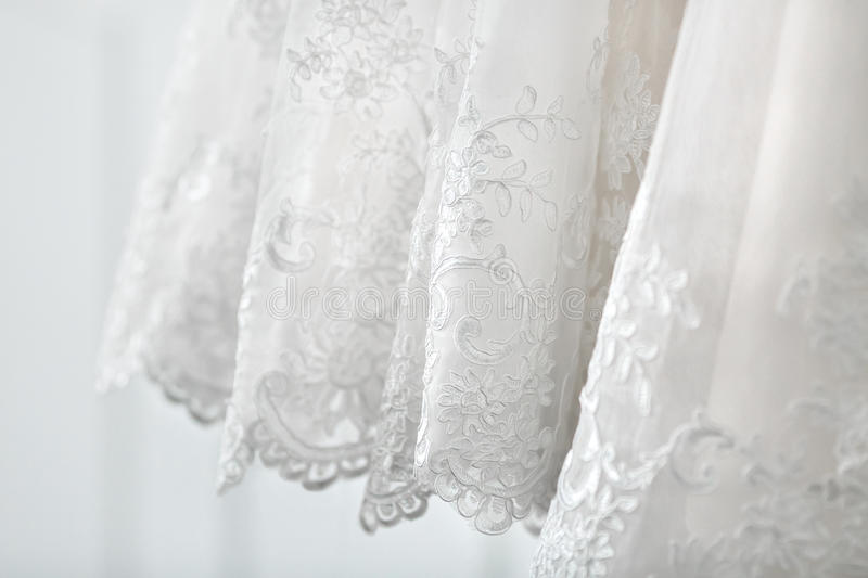 A bottom part of the white luxury bridal dress. Side view. Close-up. A bottom part of the white luxury bridal and fluffy dress. Side view. Close-up royalty free stock photography