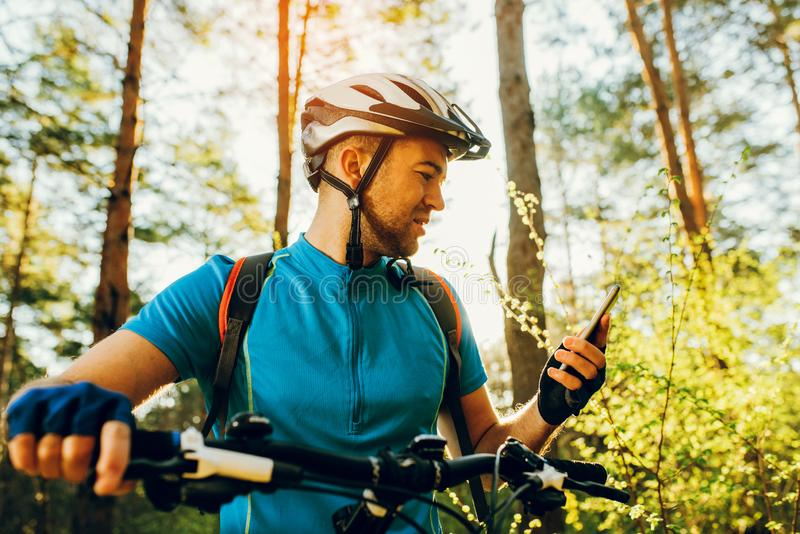 Bicyclist on bike using navigator on smart phone, explore map and search GPS coordinates while biking in mountains. Bottom and side view of bicyclist on bike stock photo