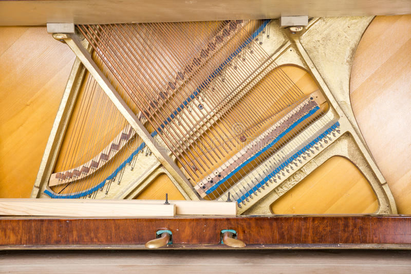 Bottom of an upright piano. Bottom structure of an upright piano: pedals, metal frame with strings, bass and treble bridges royalty free stock photos