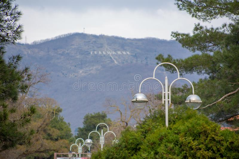 Amazing beautiful view of mountains with inscription `Gelendzhik` from city alley with beautiful lanterns and green trees royalty free stock image