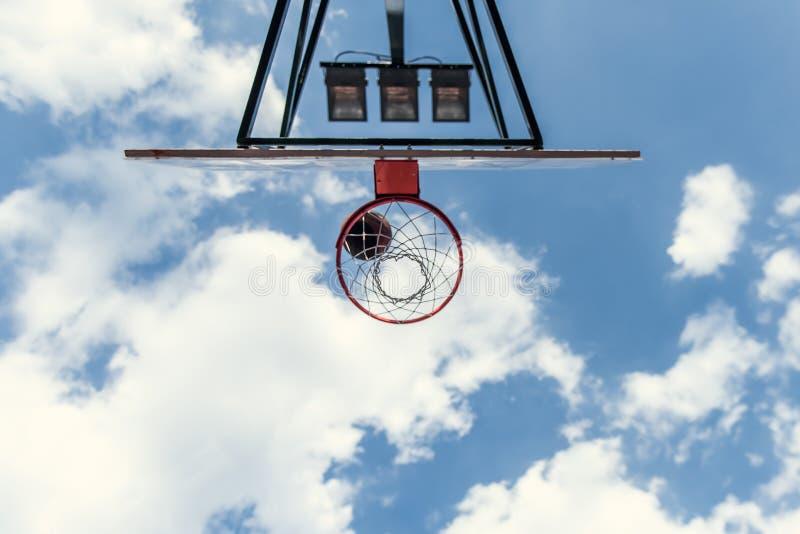 Basketball hoop outside. Bottom view of basketball hoop on blue sky background stock photo