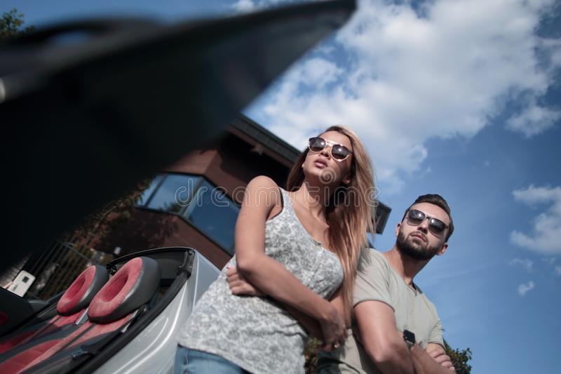 Bottom view.beautiful couple standing near a convertible car royalty free stock photography