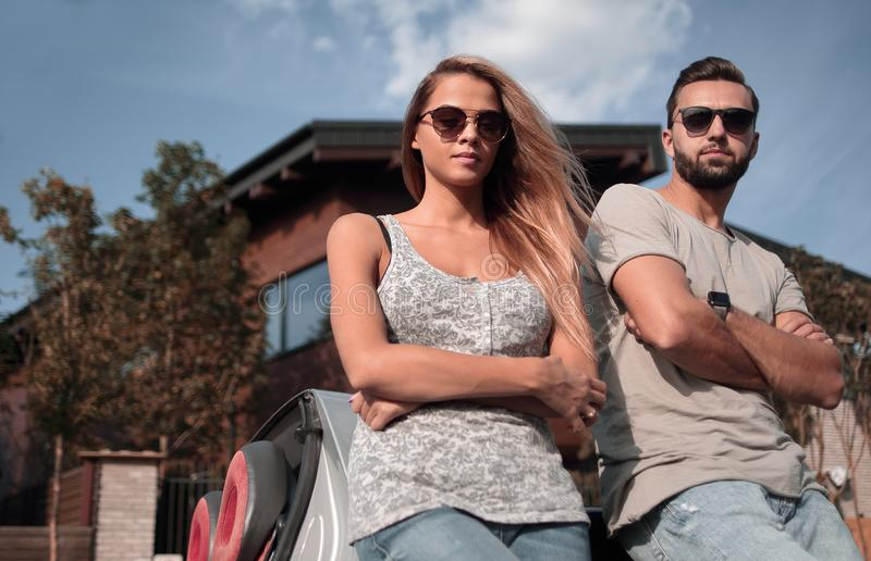 Bottom view.beautiful couple standing near a convertible car stock image