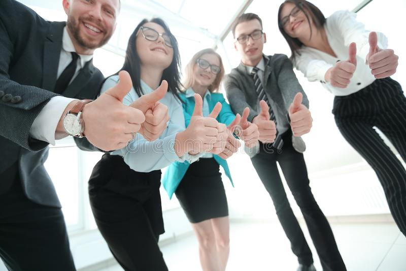 Bottom view.business team looking at the camera and showing their thumbs up. stock image