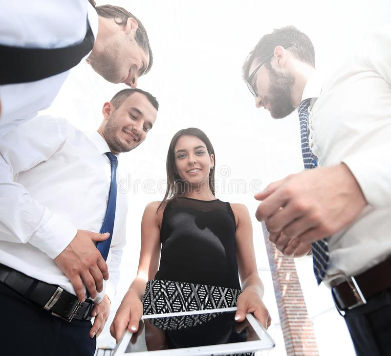 Bottom view of business team looking at digital tablet royalty free stock photo