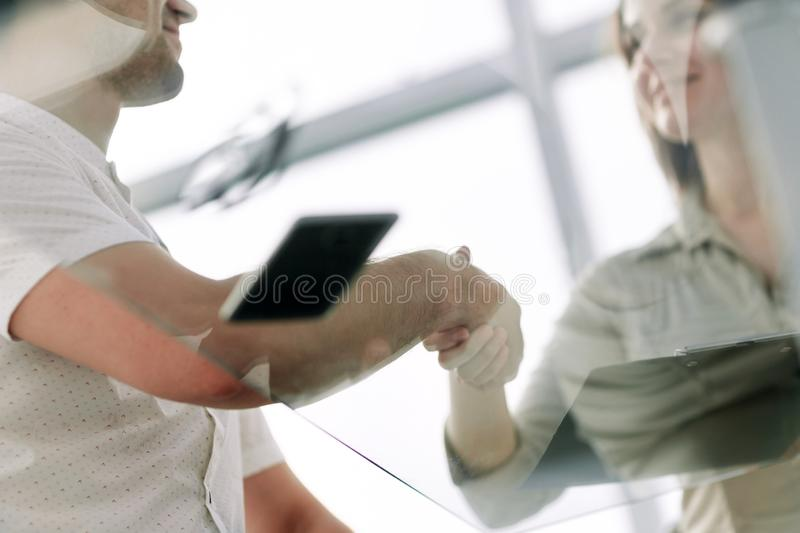 Bottom view.businessman and businesswoman shaking hands over the Desk stock photos
