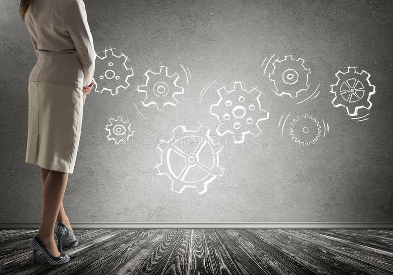 Gears mechanism as teamwork concept. Bottom view of businesswoman and teamwork drawn concept on wall stock photo