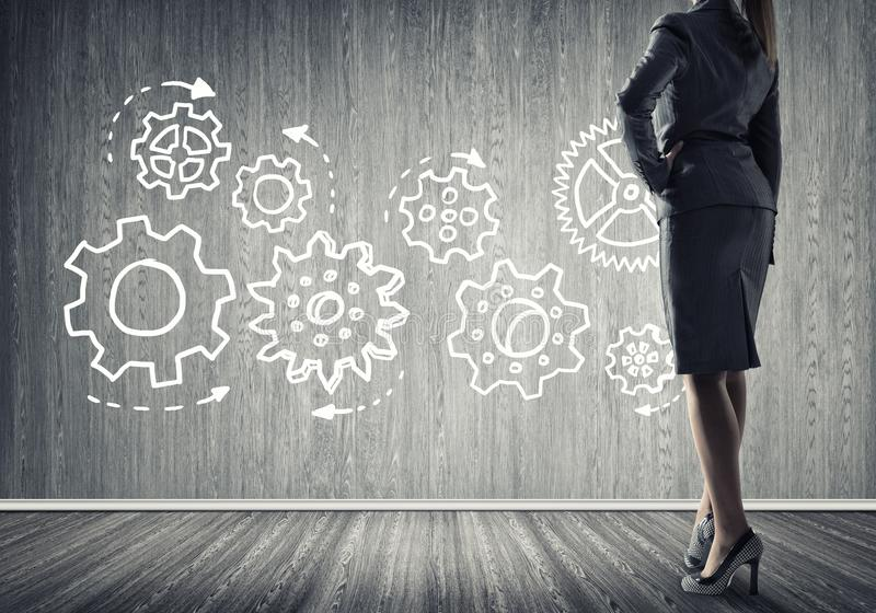 Gears mechanism as teamwork concept. Bottom view of businesswoman and teamwork drawn concept on wall stock images