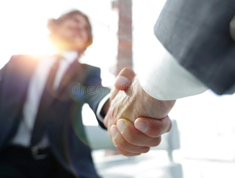 Close-up of two business people shaking hands stock images