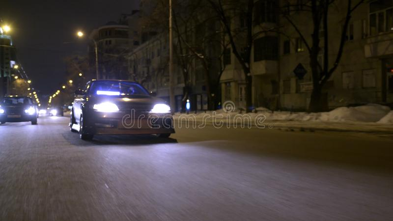 Bottom view of cool car driving on night city. Action. Shiny dark gold finish with glitter on car driving through night royalty free stock image