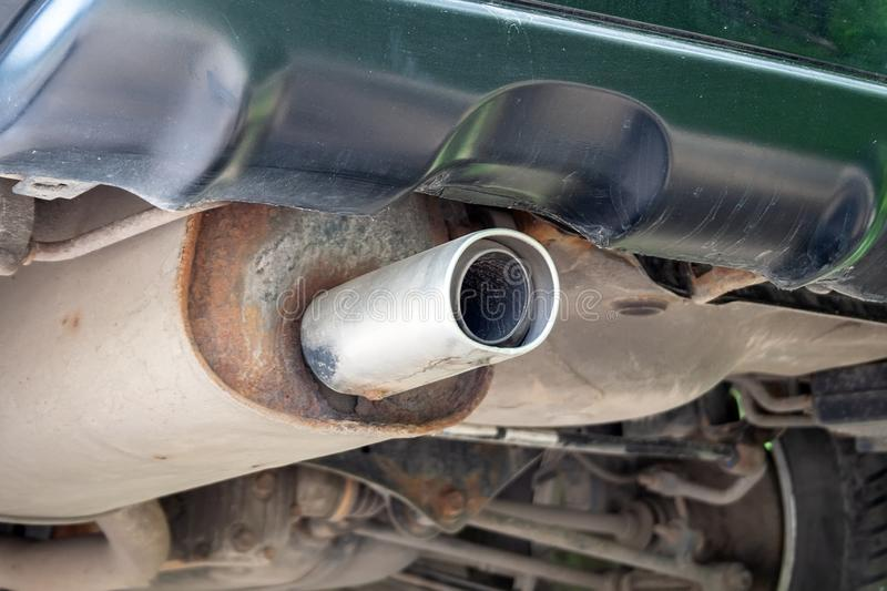 Bottom view of the exhaust pipe of the car, rusty, dusty parts and fixtures stock image