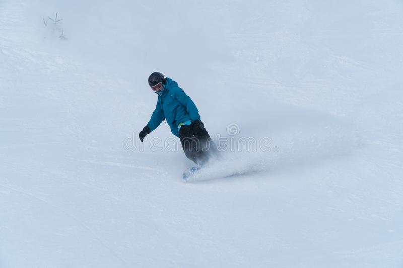 Bottom view of freeride snowboarder sliding down the snowy slope against the clear blue sky royalty free stock photo