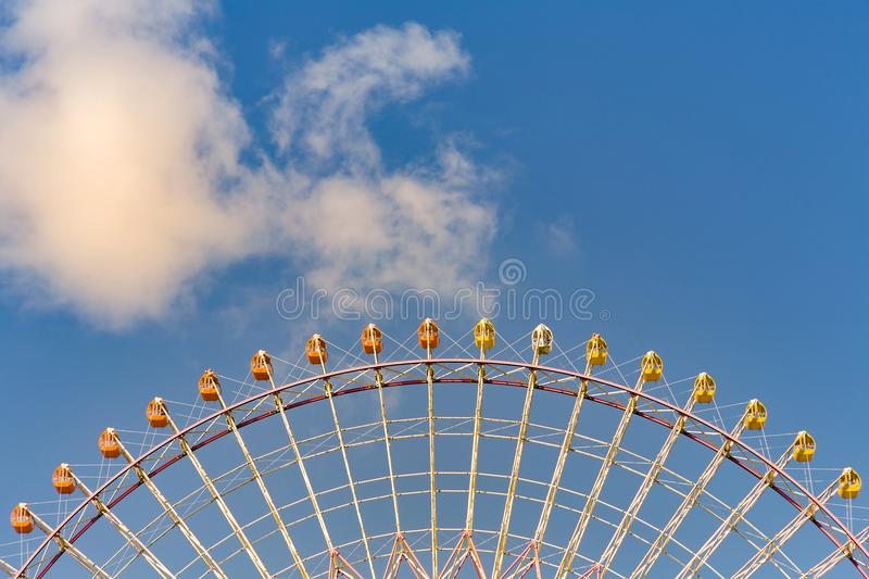 Bottom view, giant ferris wheel against blue sky. And white cloud which mean an amusement-park stock photo