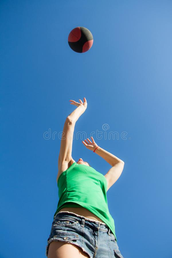 Bottom view of a girl in a jump throws a basketball over the blue sky, sports concept royalty free stock photo