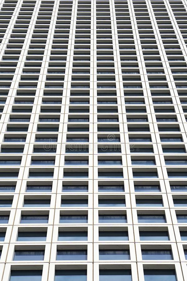 Bottom view glass grey square Windows of modern city business building skyscraper. Receding perspective, movement forward and up. Bottom view of office royalty free stock image