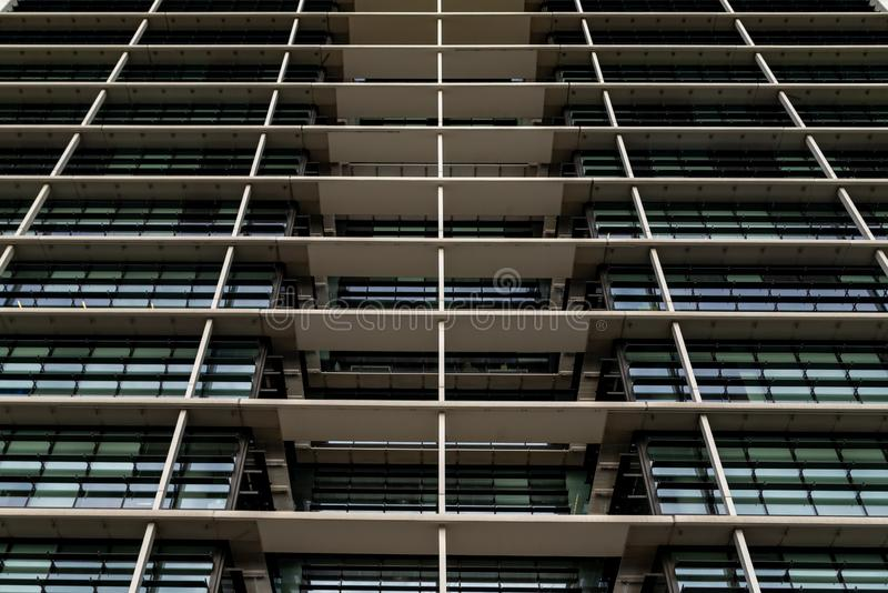 Bottom view glass grey square Windows of modern city business building skyscraper. Receding perspective, movement forward and up. Bottom view of office royalty free stock photo