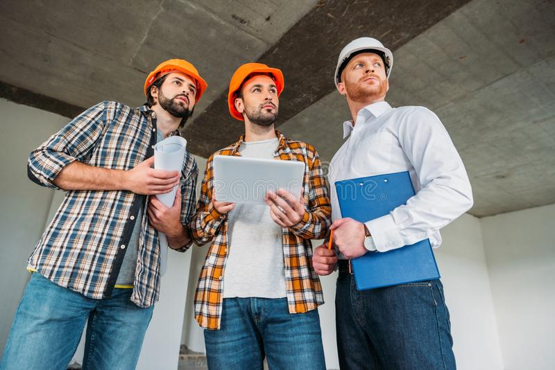 Bottom view of group of architects with tablet looking away inside of. Constructing building royalty free stock image