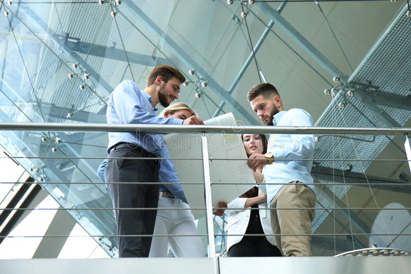 Bottom view. Modern people in casual wear having a brainstorm meeting while standing in the creative office. stock photography