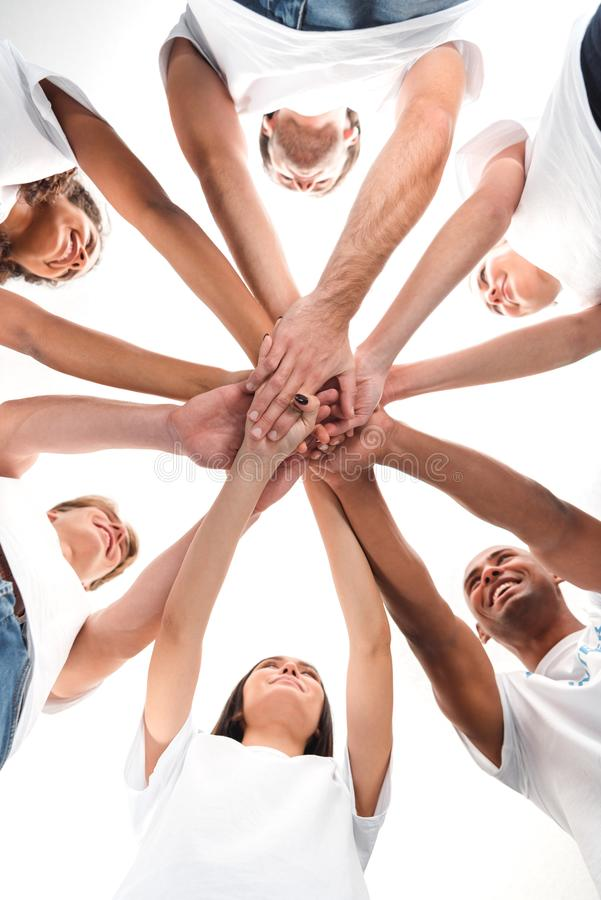 Bottom view of multiethnic group of volunteers making team gesture. Isolated on white royalty free stock photography