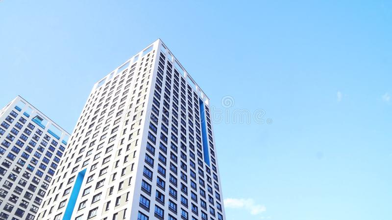 Bottom view of new residential high-rise buildings with blue sky. Urban environment. Frame. Newest residential complexes royalty free stock photo