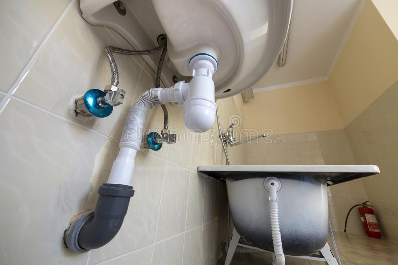 Bottom view of new white washbasin sink connected to sewer on background of bathroom light beige ceramic tiles. Professional royalty free stock photo