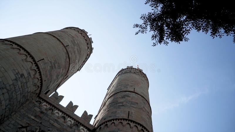 Bottom view of old fortress towers. Action. Two towers of old castle rise on background of blue sky. Beautiful and stock photography