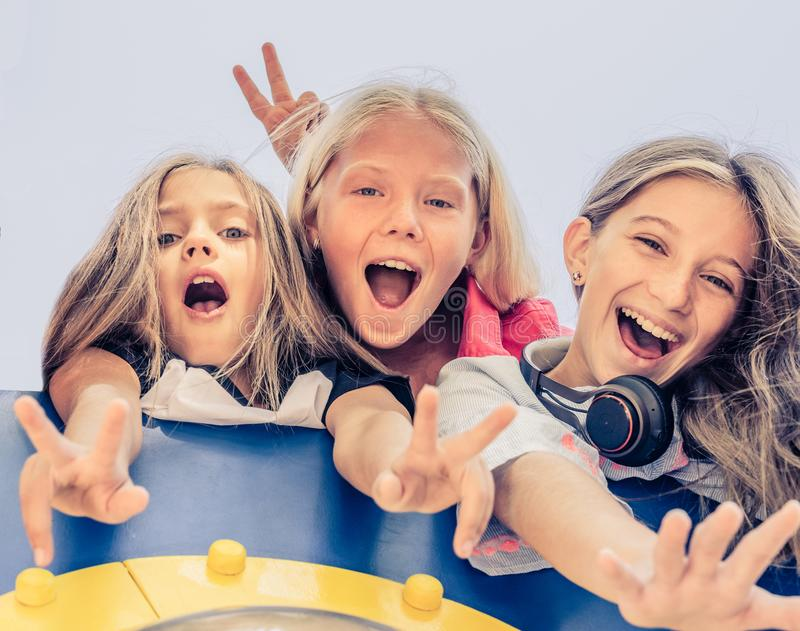 Bottom view of pretty smiling little girls standing together stock photos