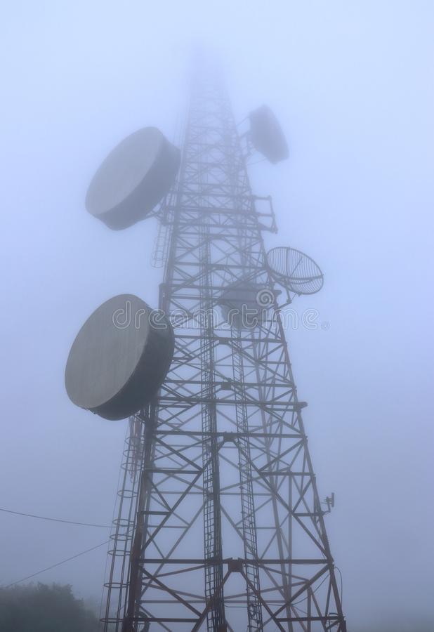 A bottom view of a radio tower in a fog. The visibility is so poor in a foggy weather that the top of a radio tower is hardly seen. It is more like the tower can royalty free stock photography