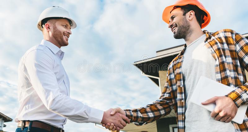 Bottom view of smiling architects shaking hands in front of. Construction site stock photo