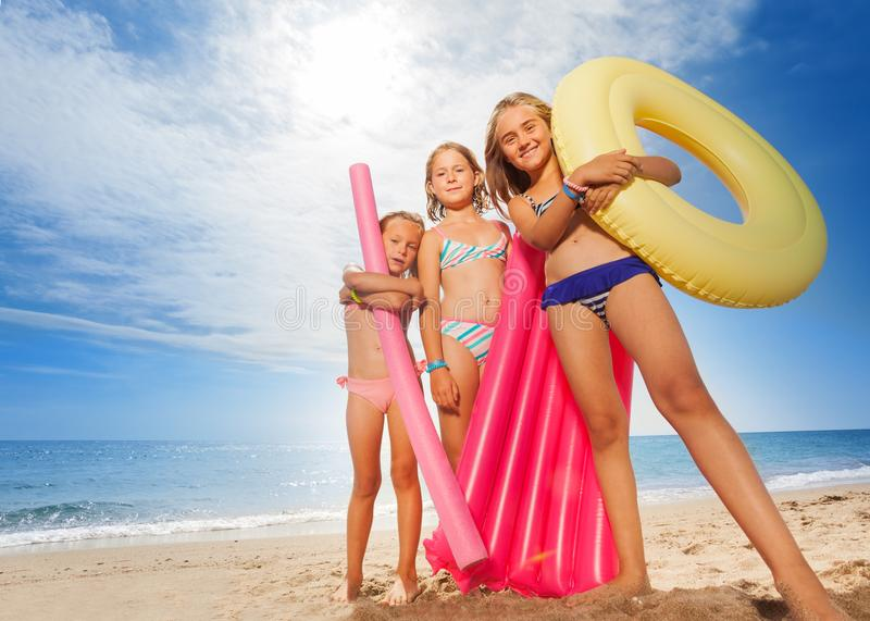 Funny girls with colorful swimming tools on beach stock photography