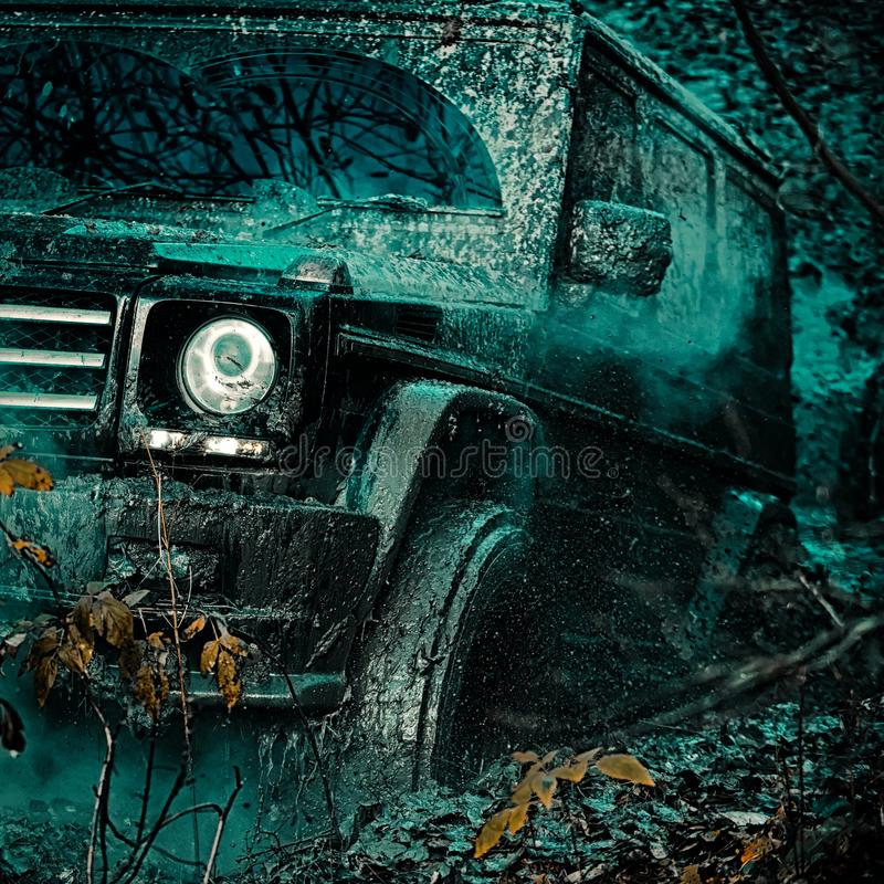 Bottom view to big offroad car wheel on country road and mountains backdrop. Jeep crashed into a puddle and picked up a. Spray of dirt. Expedition offroader royalty free stock photography