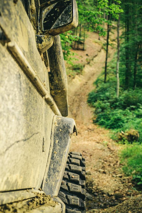 Bottom view to big offroad car wheel on country road and mountains backdrop. Offroad vehicle coming out of a mud hole. Hazard. Off-road vehicle goes on the stock image