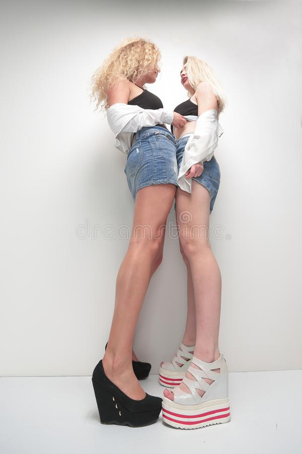 Free Bottom View.two Blonde Women Standing Near The White Wall. Royalty Free Stock Images - 115933349