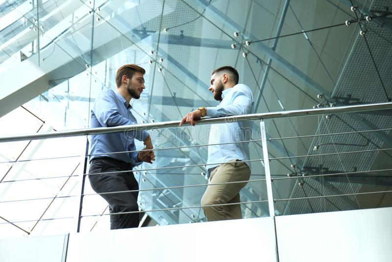 Bottom view. Two businessmen in casual wear discussing at office during business meeting. stock image