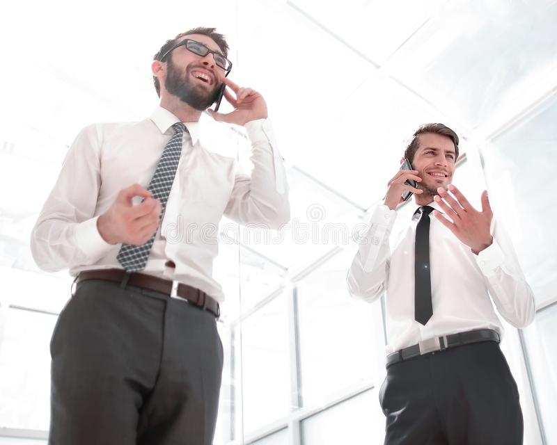 Bottom view.two successful businessmen talking on their smartphones. royalty free stock photography