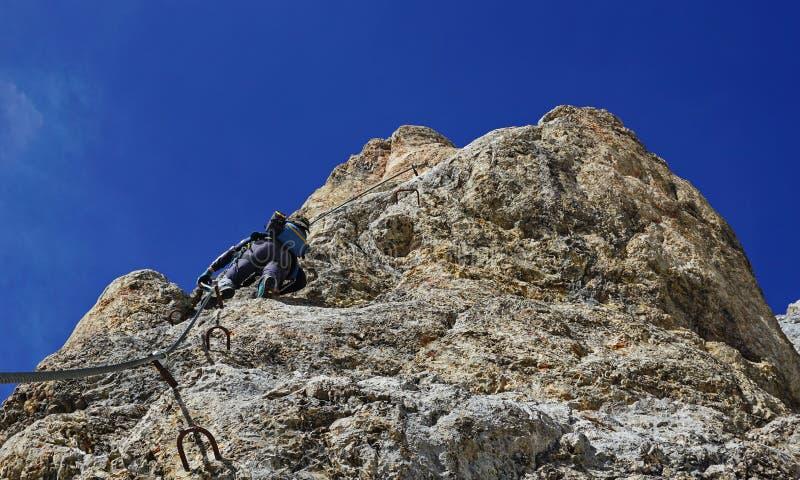 Via ferrata climber on a rock top view stock photo