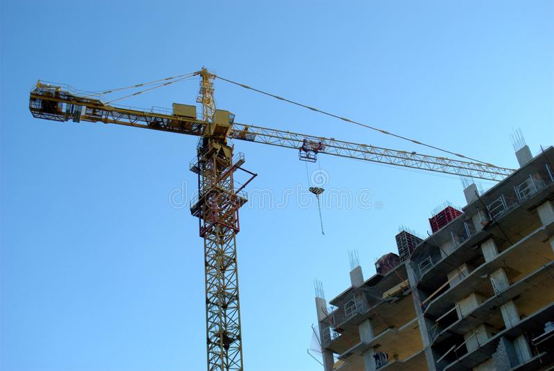 Bottom view of a tower crane and a high-rise apartment building under construction in the morning sun against a blue sky. Bottom view of a yellow tower crane royalty free stock images