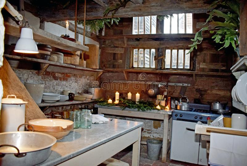 A cluttered Tudor kitchen. The bottom of the wooden stair case can be seen in the left side of this basement Tudor kitchen, to the front is very large wooden stock images