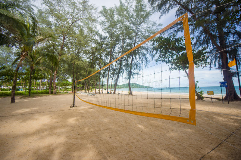 Bottom of yellow voleyball net on beach among palm trees royalty free stock photo