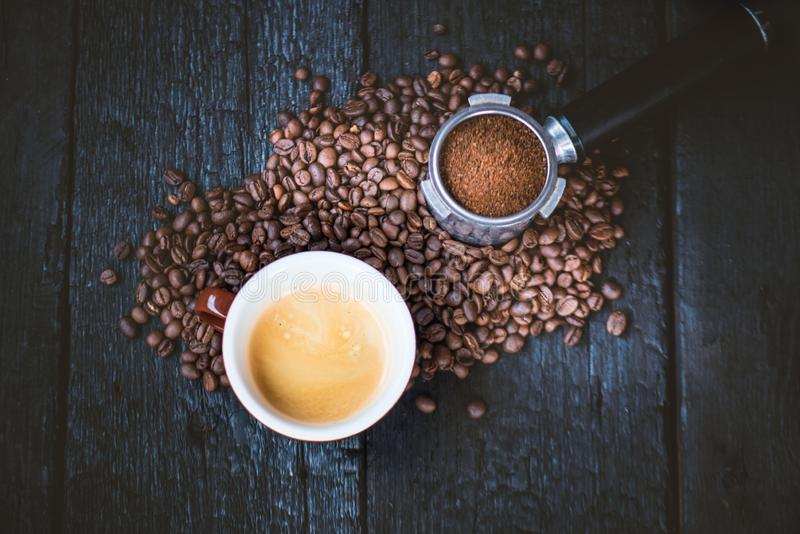 Bottomless filter with grind beans on a wooden black table and cup of espresso coffee. Roasted coffee beans. Espresso coffee extra royalty free stock image
