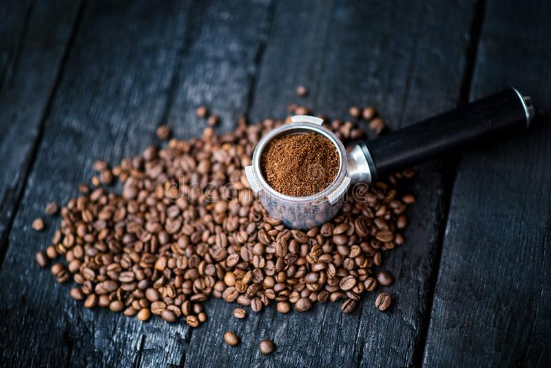 Bottomless filter with grind beans on a wooden black table. Roasted coffee beans. Espresso coffee extraction. Prepare of espresso. stock photo