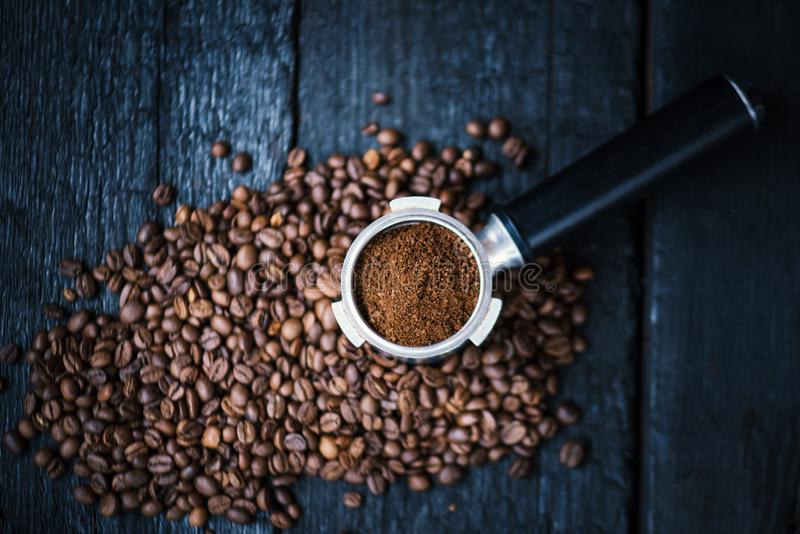 Bottomless filter with grind beans on a wooden black table. Roasted coffee beans. Espresso coffee extraction. Prepare of espresso. royalty free stock photos