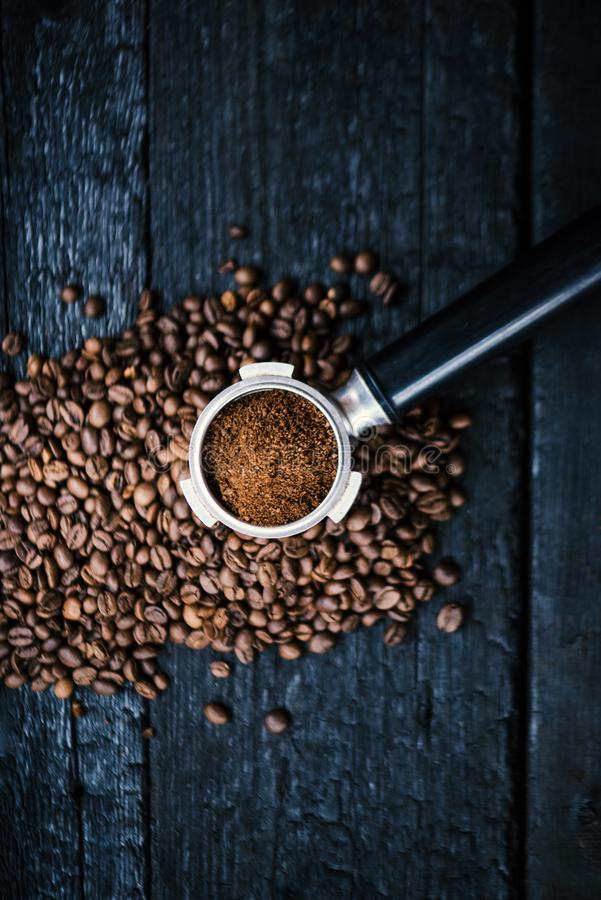 Bottomless filter with grind beans on a wooden black table. Roasted coffee beans. Espresso coffee extraction. Prepare of espresso. royalty free stock image