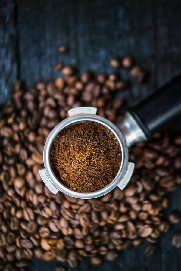 Bottomless filter with grind beans on a wooden black table. Roasted coffee beans. Espresso coffee extraction. Prepare of espresso. royalty free stock photo