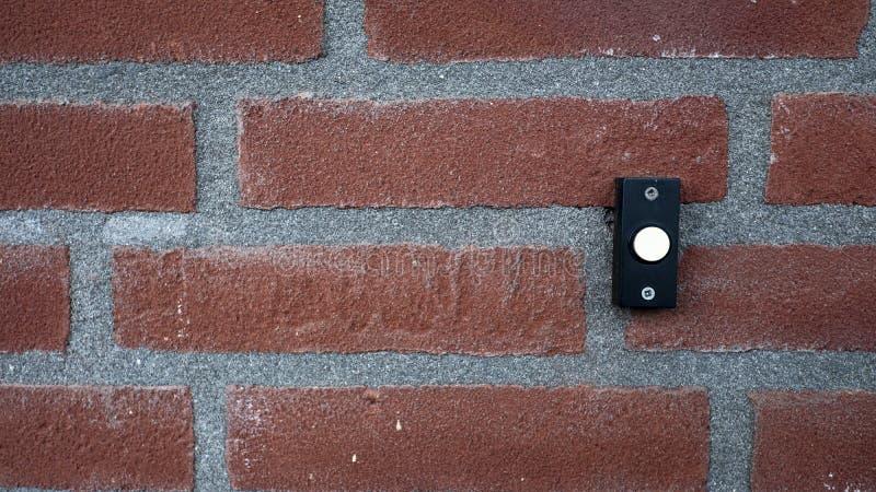 Bottone del campanello su una parete esterna di pietra immagini stock