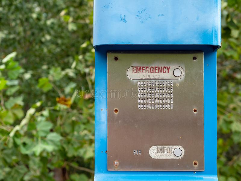 Bottone di emergenza, bottone di informazioni ed altoparlante su una posta blu di emergenza fotografia stock
