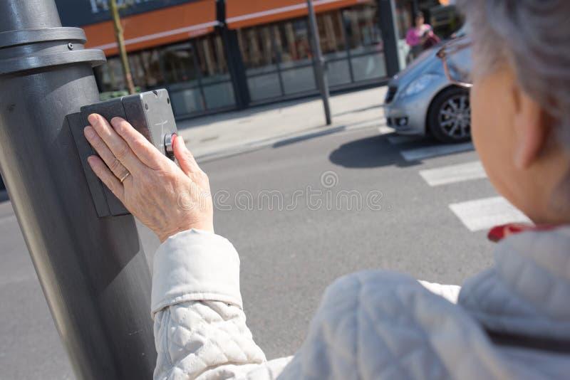 Bottone premente pedonale anziano per attraversare strada immagini stock