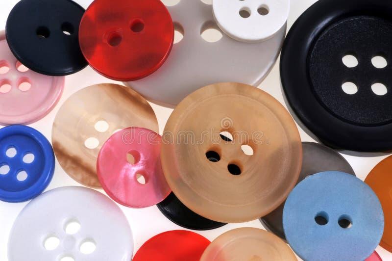Bottoni di plastica delle dimensioni e dei colori differenti in primo piano immagini stock