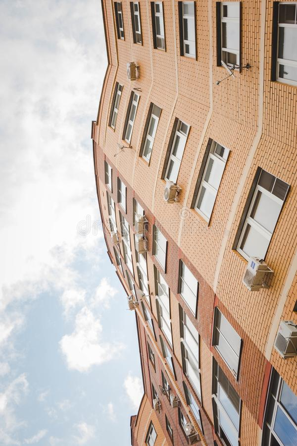 Bottow view of facade of new multi-storey residential building with bakconies made of biege brick. Bottow view of facade of new multi-storey residential royalty free stock image