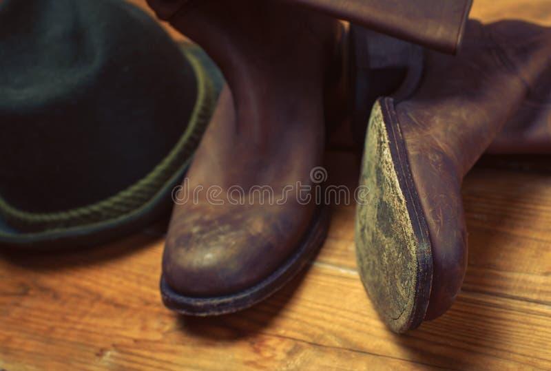 Botts de cowboy occidental de rodéo et chapeau bruns sales et utilisés photographie stock